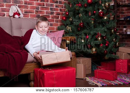 The boy woke up and saw a lot of gifts from Santa Claus
