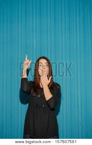 Portrait of young woman with shocked facial expression over blue studio background pointing up