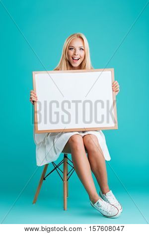 Full length portrait of a cheerful smiling woman holding blank board while sitting on chair isolated on the blue background
