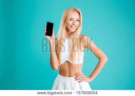 Portrait of a happy casual woman showing blank smartphone screen isolated on the blue background