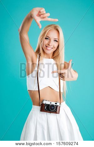 Portrait of a smiling cheerful girl with retro camera making frame gesture with fingers isolated on the blue background