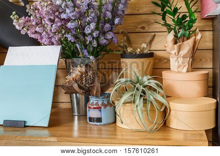 Small business. Modern flower shop interior. Floral design studio, decorations and arrangements. Flowers delivery service and sale of home plants in pots, wooden showcase with present boxes closeup.
