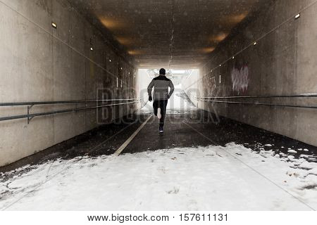 fitness, sport, people, season and healthy lifestyle concept - young man running along pedestrian subway tunnel in winter