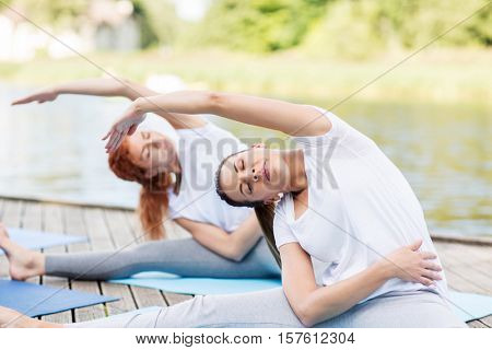 fitness, sport, people and healthy lifestyle concept - women making yoga exercises outdoors on river or lake berth