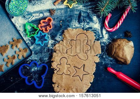 Step of making traditional Christmas gingerbread cookies. Raw dough and cutters for the holiday cookies on a dark table. Preparing Christmas gingerbread cookies. Xmas time background. Top view.