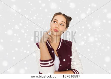 winter, christmas, people and teens concept - happy pretty teenage girl thinking over gray background and snow