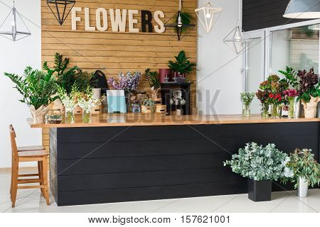 Small business. Modern flower shop interior, reception desk. Floral design studio, sale of decorations and arrangements. Flowers delivery service and sale of home plants in pots, wooden showcase.