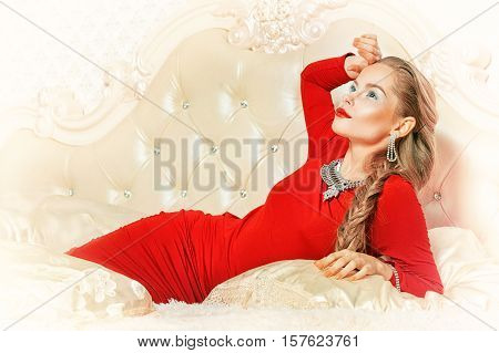 Beautiful young woman with stylish make up, elegant jewelry and in red dress posing on bed