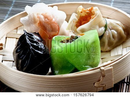 Various Dim Sum in Bamboo Steamed Bow in Shadow closeup on Straw Mat background