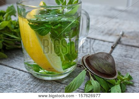 Mint tea with lemon mint and tea strainer. Winter warming soothing drink.