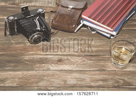 Old-fashioned photocamera with leather case and notebooks on vintage wood background