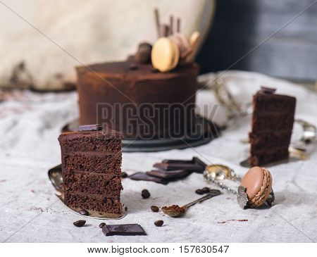 Slice of an ultimate chocolate cake, French macaron, cocoa and coffee beans