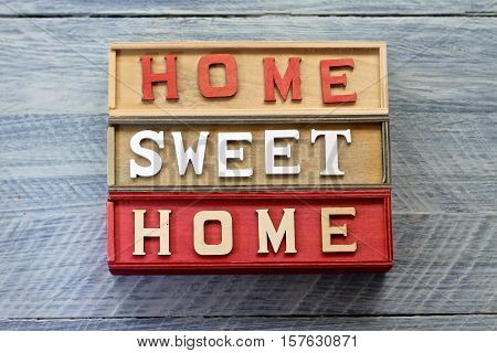 Home Sweet Home wooden sign on blue rustic background