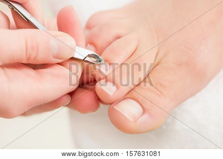 Pedicure procedure nipping cuticles, toned image, close up