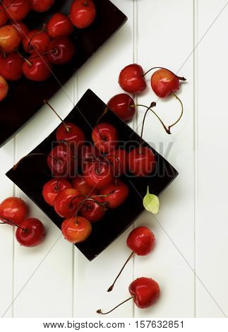 Arrangement of Two Black Plates with Fresh Ripe Sweet Maraschino Cherries closeup on Plank White background. Top View