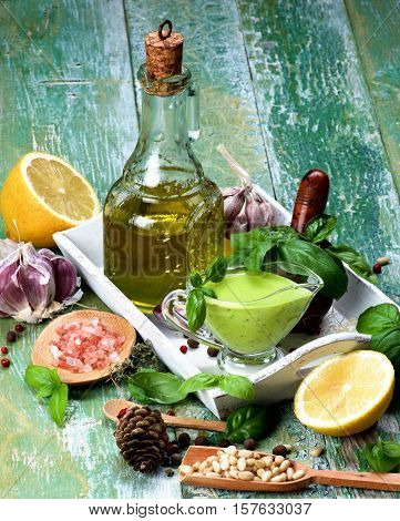 Arrangement of Freshly Made Creamy Pesto Sauce in Glass Gravy Boat with Ingredients Spices and Olive Oil in White Wooden Tray closeup on Green Cracked Wooden background