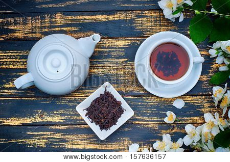 Black tea in a white cup and saucer and jasmine flowers top view