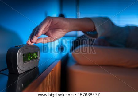 Woman pressing snooze button on early morning digital alarm clock poster