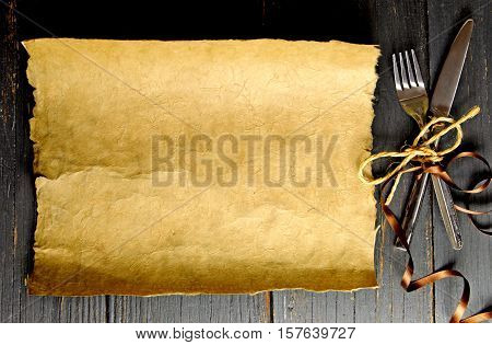 Chistmas menu scroll background with satin ribbon around cutlery