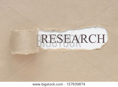 Torn paper uncovering the word research underneath