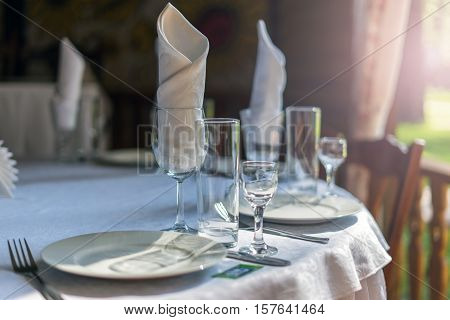 Table setting at a banquet empty plates glasses cutlery napkins summer terrace. Restaurant courtyard. The banquet area