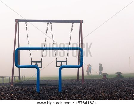 KIRKBY IN ASHFIELD ENGLAND - OCTOBER 31: People walking in fog near childrens' play park England. In Kirkby In Ashfield Nottinghamshire England. On 31st October 2016.