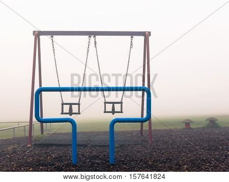 KIRKBY IN ASHFIELD ENGLAND - OCTOBER 31: Empty childrens' play park in the fog England. In Kirkby In Ashfield Nottinghamshire England. On 31st October 2016.