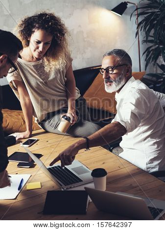 Team of coworkers making great work discussion in modern office.Young business teamwork concept.Bearded man talking with creative director and account manager.Vertical, blurred background
