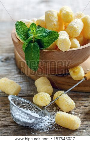 Sieve With Powdered Sugar And Corn Sticks In A Bowl.