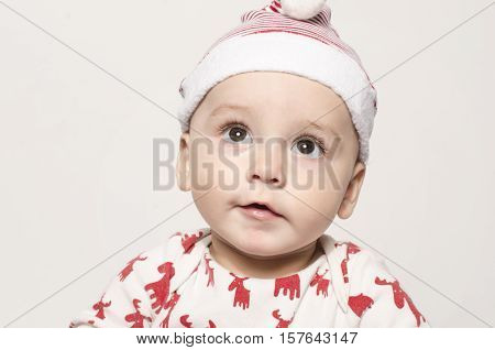 Portrait of a cute baby boy looking up thinking wearing a Santa hat.  Adorable child wearing a blouse with reindeer and a red hat ready for Christmas.