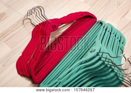 Pile of hangers arranged on the floor. Close up on colorful felt hangers.