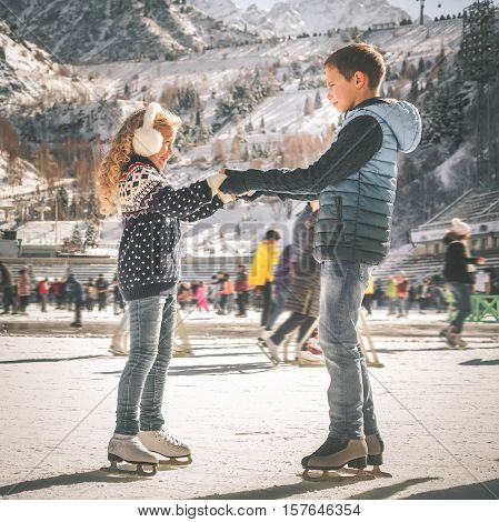 Happy children ice skating at ice rink outdoor, figure skating, at winter day, sport and healthy lifestyle, ice skating at Holland. Funny kids, boy and girl, sister and brother. Family poster