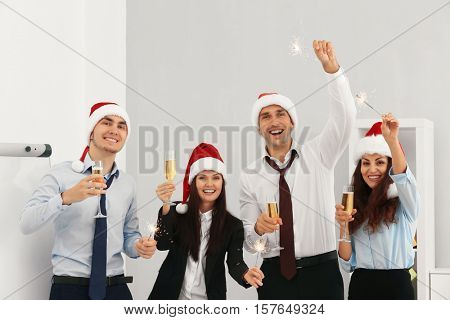 Business people in Santa hats with sparklers at office party