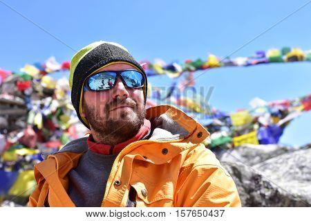 Portrait of a trekker at high mountain, buddhist prayer flags background.