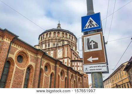 street sign to Milan's famous church Santa Maria Delle Grazie, hosting in it's refectory, The Last Supper mural painting by Leonardo da Vinci. street side view with blue sky.