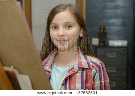 Smiling young artist girl draw in the workshop