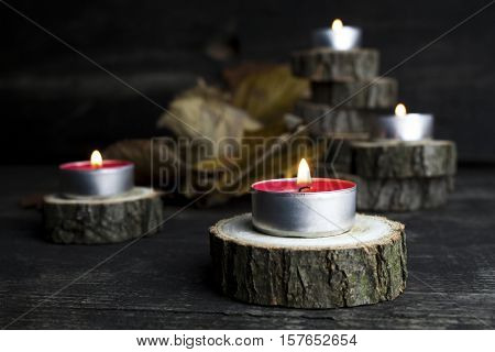 Christmas Candles Burning, Decoration With Wooden Logs Resting On Rustic Wooden Background