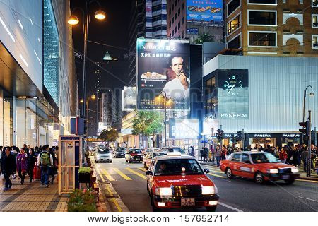 Taxi And Illuminated Signs On Streets Of Night City Hong Kong