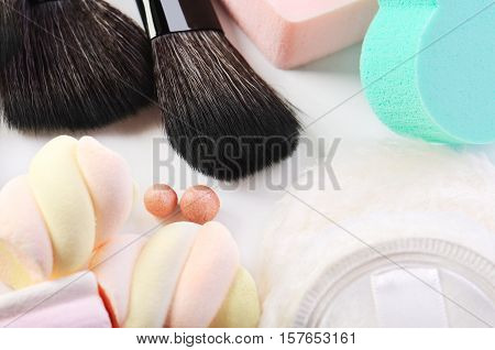 Makeup Brushes, Rouge Balls, Sponges Heart Shape,  Powder Puff And Some Candies On A White Backgroun