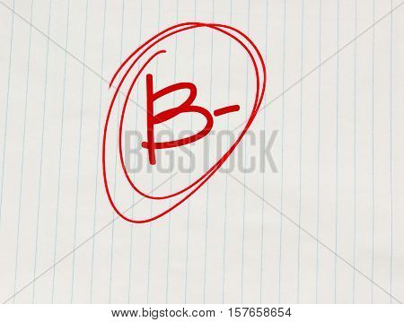 B minus (B-) grade written in red on notebook paper
