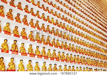 Wall With Small Golden Buddha Statues Inside The Temple Of The Ten Thousand Buddhas Monastery In Hon