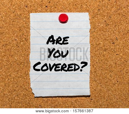 The words Are You Covered? typed on a scrap of lined paper and pinned to a cork notice board. Asking the question, are you insured for your car, travel, home or other liability