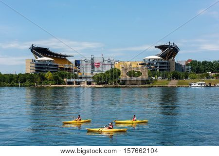 PITTSBURGH - JULY 22: Three people kayaking in the Allegheny River in front of Heinz Field, home of the Pittsburgh Steelers on July 22, 2016 in Pittsburgh, PA