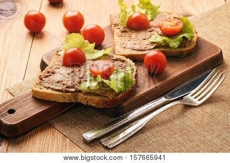 Chicken liver pate on the bread on wooden tray.