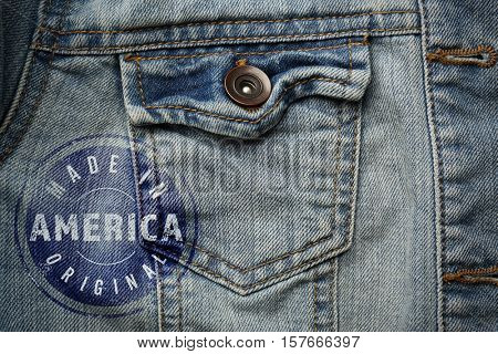 Printed text MADE IN AMERICA ORIGINAL on jeans jacket, closeup. Manufacturing quality concept.