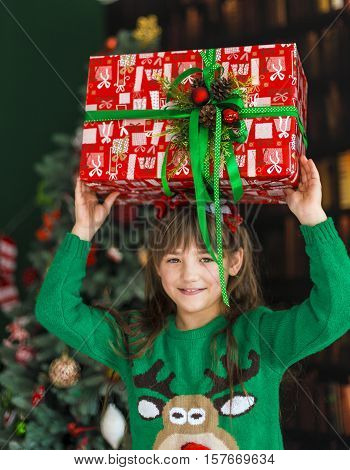 Kid girl holding surprize gift box before christmas tree
