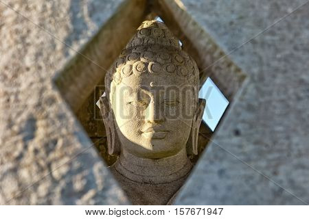 Carved stone buddha statue inside small stupa. Frontal view