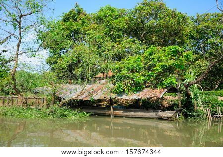 A covered area protecting a boat within the Mekong river delta in Vinh Long area of South Vietnam on a sunny day.