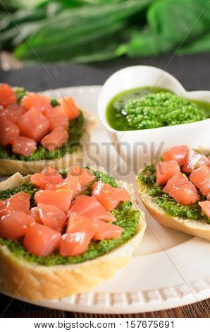 Crunchy tasty bruschetta with pices of salmon and pesto sauce on a slate plate vertical