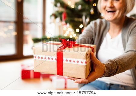 Unrecognizable senior woman sitting on the floor in front of illuminated Christmas tree inside in her house giving present.